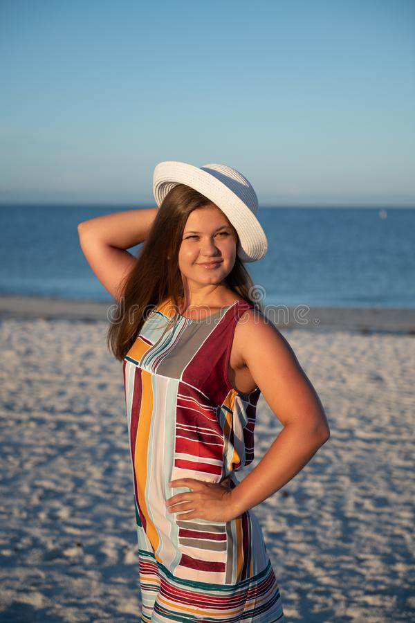 Young woman on the beach. Portrait of a young  beautiful carefree woman walking on sunny beach wearing dress and hat stock photo