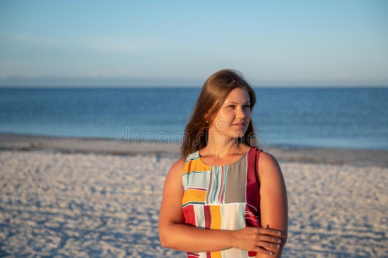 Young woman on the beach. Young woman wearing a dress  thinking and looking away on the beach royalty free stock image