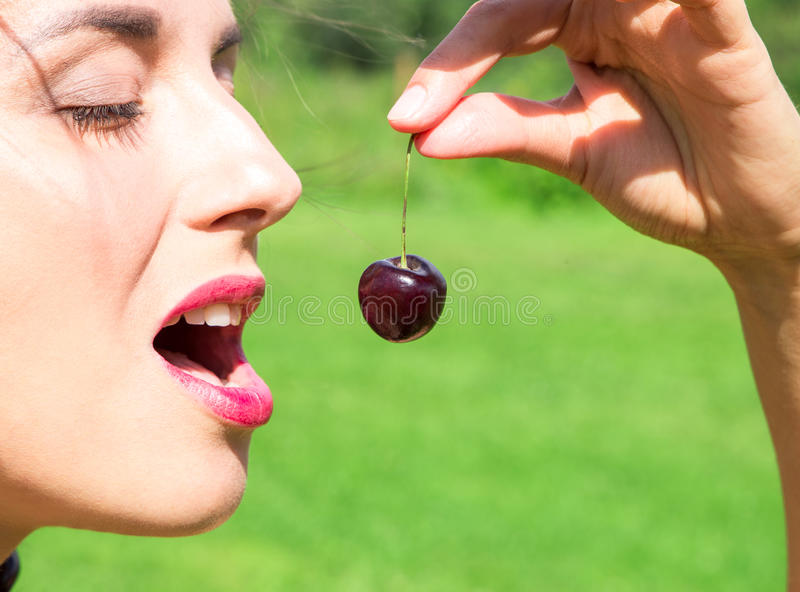 Young woman in beads made of fresh cherry holding cherry on open mouth with summer green forest background. Close up of young woman in beads made of fresh cherry royalty free stock image