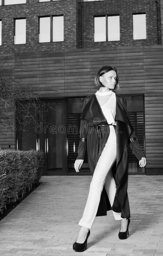 A young woman in a beautiful black coat and white trousers walking down the street royalty free stock photos