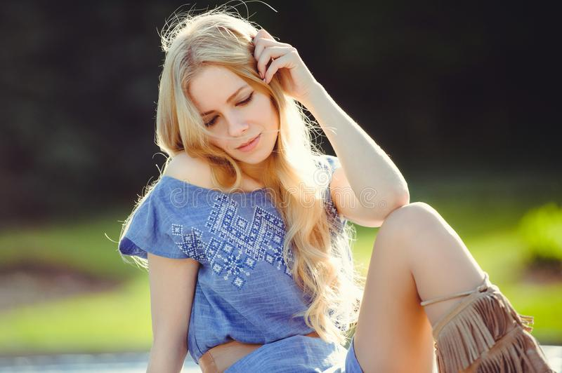 Young woman with beautiful blonde straight long sun playing hair sitting on the lawn thoughtful stock photography