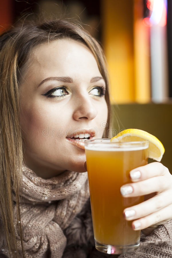 Young Woman with Beautiful Blue Eyes Drinking Hefeweizen Beer royalty free stock images