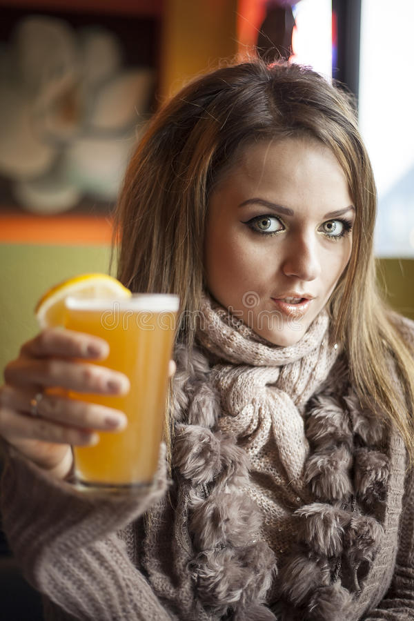 Young Woman with Beautiful Blue Eyes Drinking Hefeweizen Beer stock photography