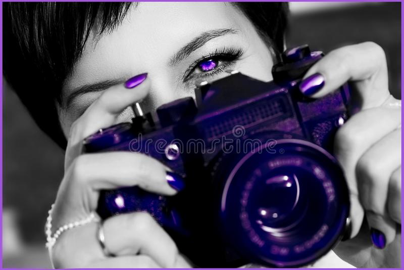 Young woman with beautiful bright eyes takes photo on the camera. Fashionable ultraviolet artistic image. stock image