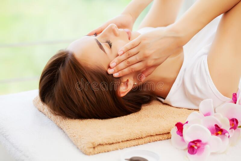Young woman with beautiful face on facial massage in beauty studio royalty free stock photos