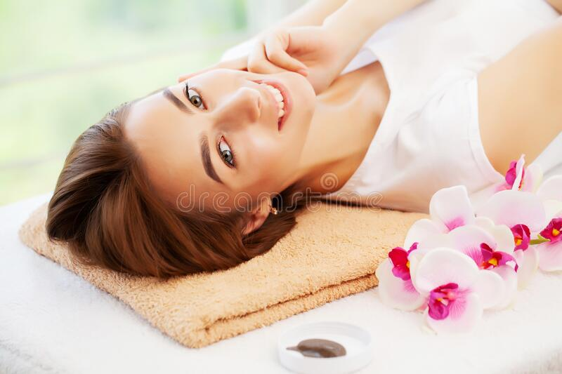 Young woman with beautiful face on facial massage in beauty studio royalty free stock photography