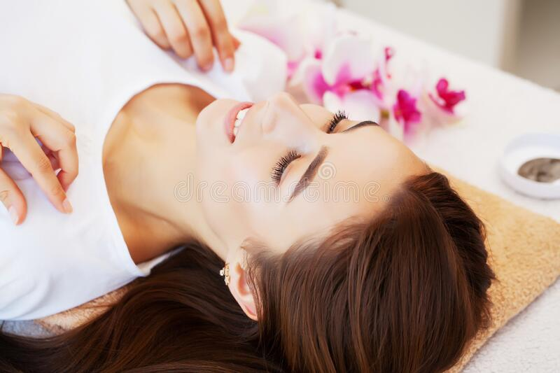 Young woman with beautiful face on facial massage in beauty studio royalty free stock images