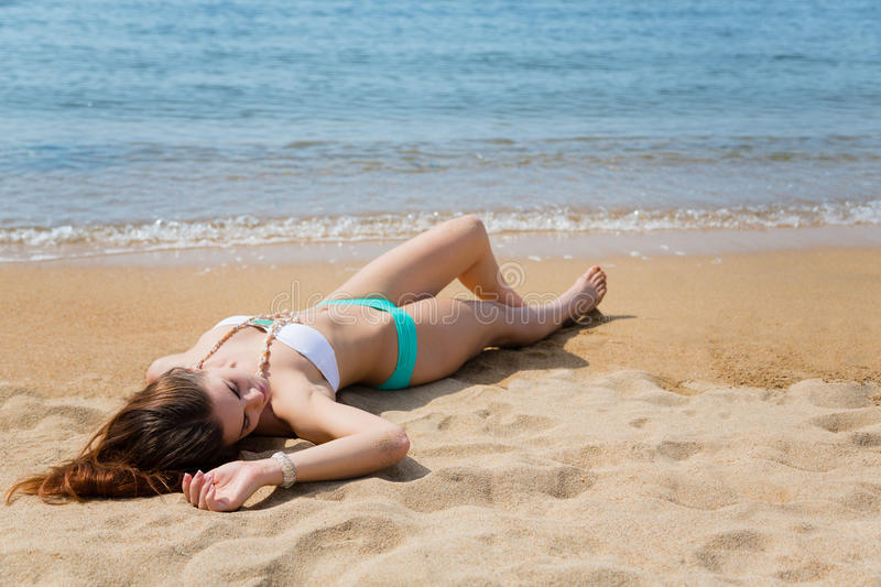 Young woman beautiful girl lies on the beach stock image