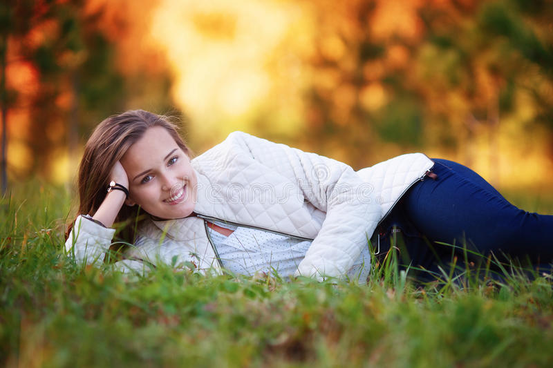 Young woman, beautiful girl lying on grass in autumn park royalty free stock photography