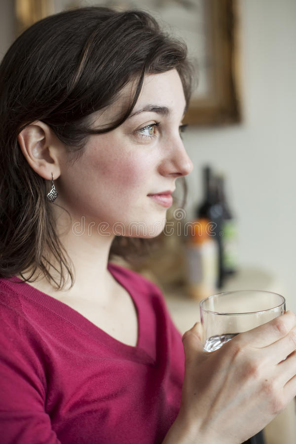Young Woman with Beautiful Green Eyes Drinking Water royalty free stock image