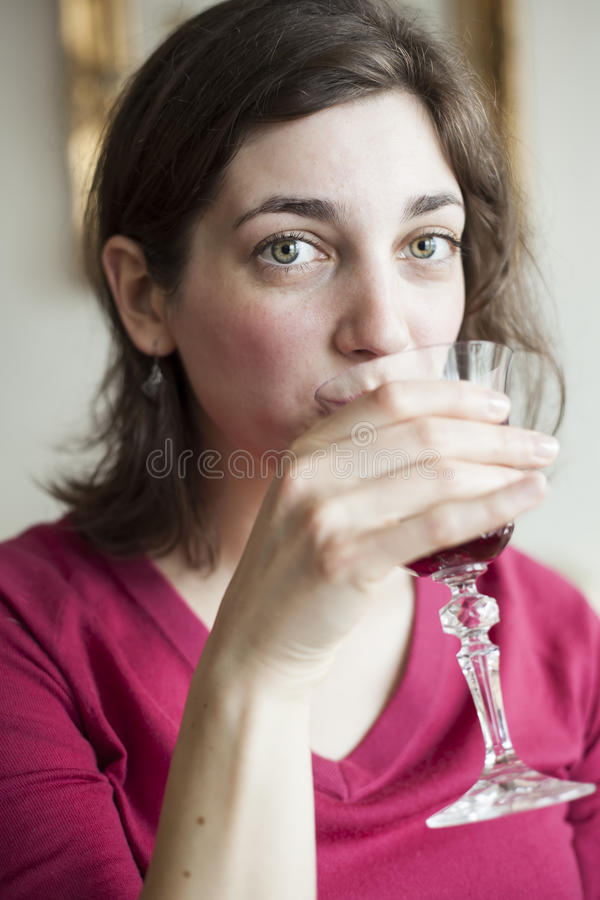 Young Woman with Beautiful Green Eyes Drinking Wine stock photography