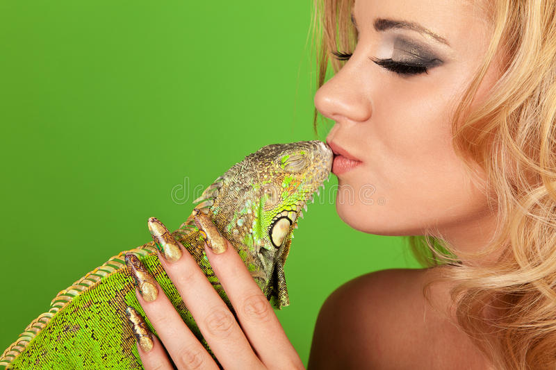 Young woman with beautiful manicure kissing a igua