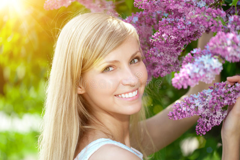 Young woman with a beautiful smile with healthy teeth with flowers. Face of a beautiful positive girl Concept on the subject royalty free stock photos
