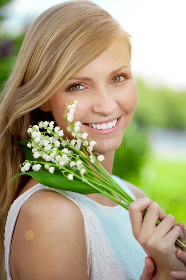 Young woman with a beautiful smile with healthy teeth with flowers. Face of a beautiful positive girl Concept on the subject royalty free stock image
