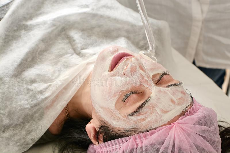 Young woman in beauty salon does rejuvenating, toning procedure darsonval on the face royalty free stock photos