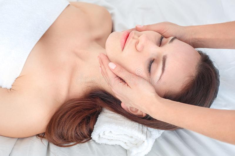 Young woman at beauty salon lying getting face massage close-up stock photo