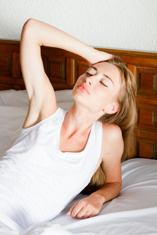 Young woman in a bed royalty free stock photo