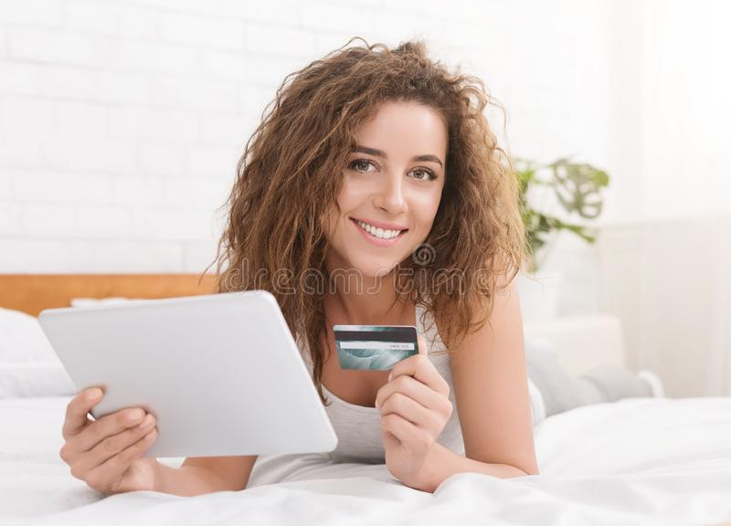 Young woman in bed doing online shopping with digital tablet stock image