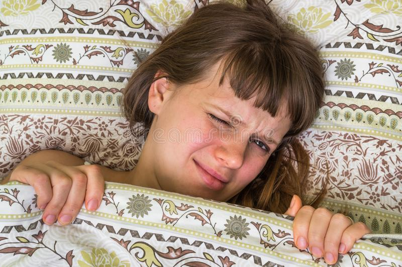 Young woman in bed having headache royalty free stock images