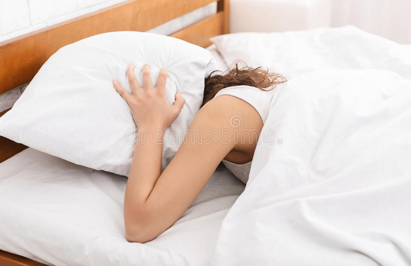Young woman in bed hiding under pillow royalty free stock photo