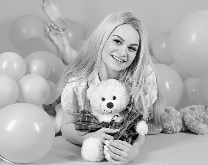 Young woman on bed hugging teddy bear. Birthday girl concept. Blonde on smiling face relaxing with teddy bear toy. Woman. Cute celebrate birthday with balloons stock image
