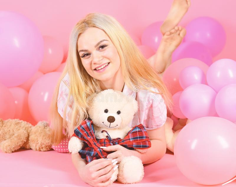 Young woman on bed hugging teddy bear. Birthday girl concept. Blonde on smiling face relaxing with teddy bear toy. Woman. Cute celebrate birthday with balloons stock photography