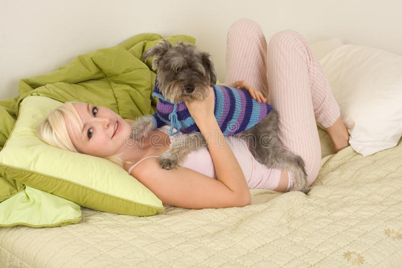 Young woman in bed playing with schnauzer dog royalty free stock photography