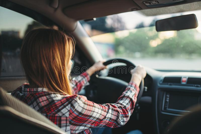 Young woman beginner driving a car, back view royalty free stock image