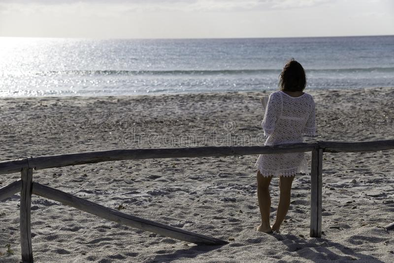 Young woman from behind reads a book on the beach looking at the horizon at dawn in the wind, dressed in a white lace dress, white. Underwear and long hair royalty free stock photos
