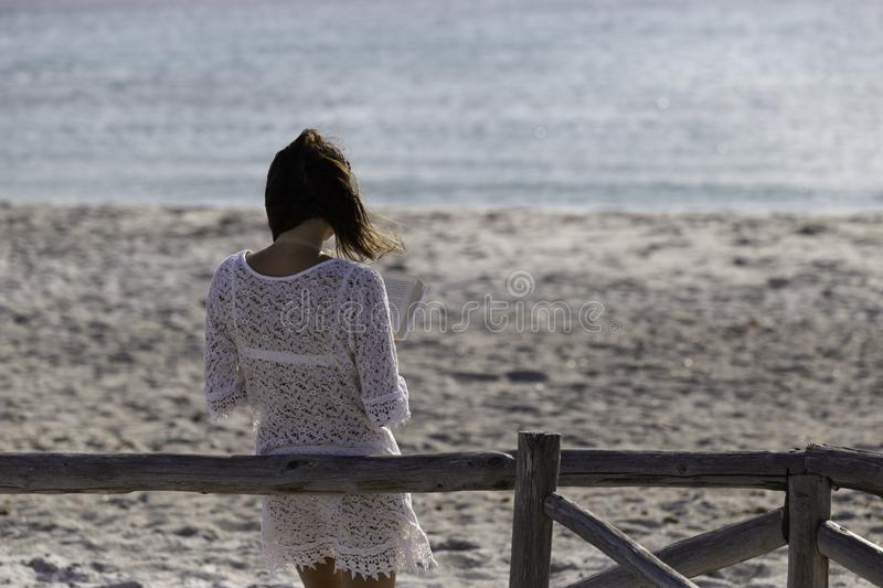 Young woman from behind reads a book on the beach looking at the horizon at dawn in the wind, dressed in a white lace dress, white. Underwear and long hair stock photo
