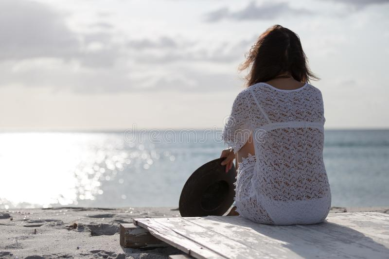 Young woman from behind sitting by the sea looks at the horizon at dawn in the wind, dressed in a white lace dress and white. Underwear and long hair royalty free stock photography