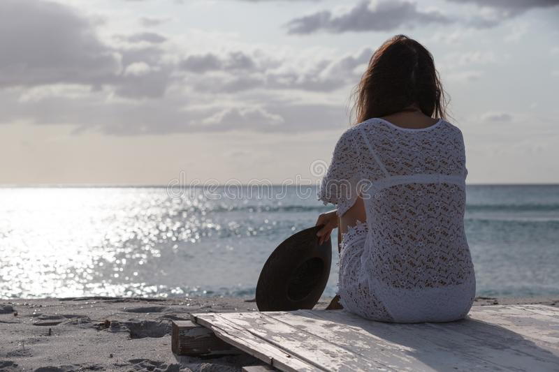 Young woman from behind sitting by the sea looks at the horizon at dawn in the wind, dressed in a white lace dress and white. Underwear and long hair royalty free stock photo