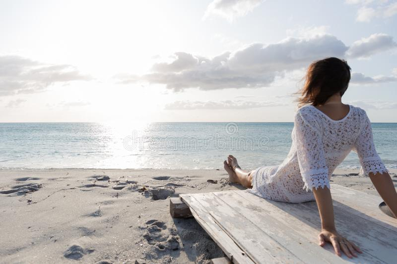 Young woman from behind sitting by the sea looks at the horizon at dawn in the wind, dressed in a white lace dress and white royalty free stock photography
