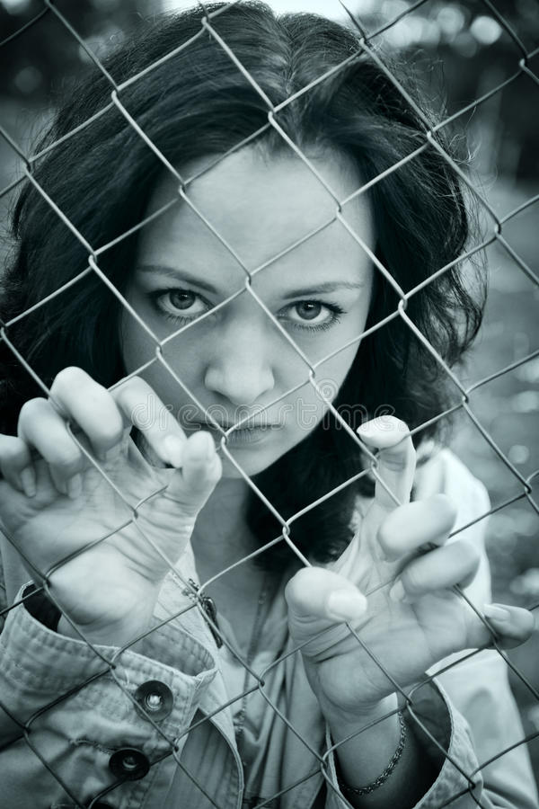Young woman behind wire stock photography