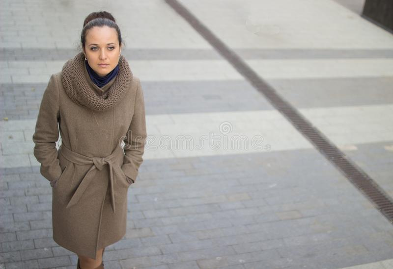 A young woman in a beige coat walks thoughtfully down the street royalty free stock image