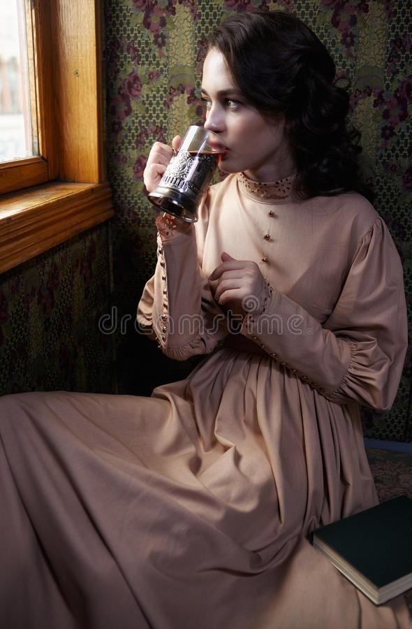 Young woman in beige vintage dress of early 20th century drinkin. G tea in coupe of retro railway train royalty free stock photos