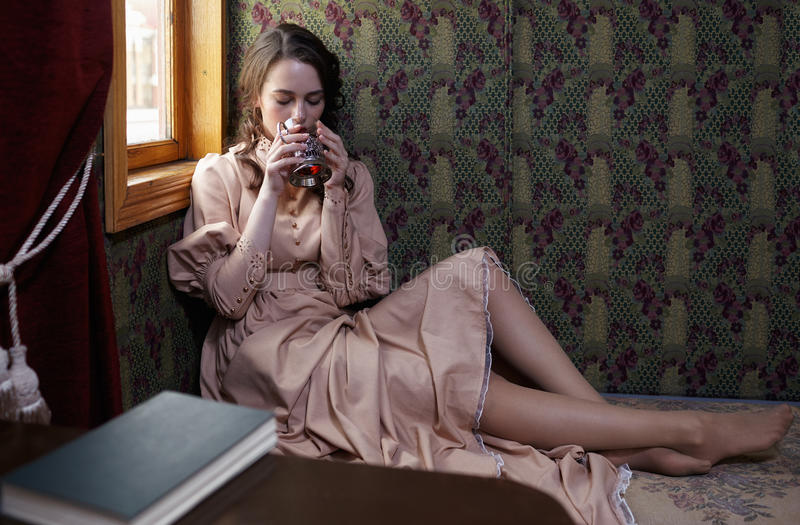 Young woman in beige vintage dress of early 20th century drinkin. G tea in coupe of retro railway train stock photos