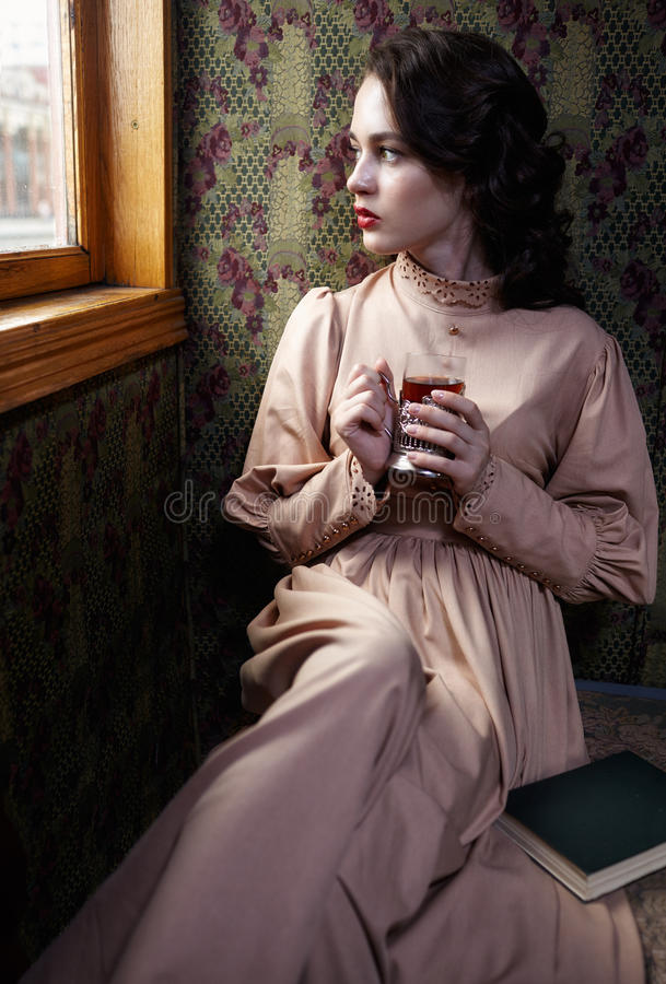 Young woman in beige vintage dress of early 20th century drinking tea in coupe of retro railway train royalty free stock photos