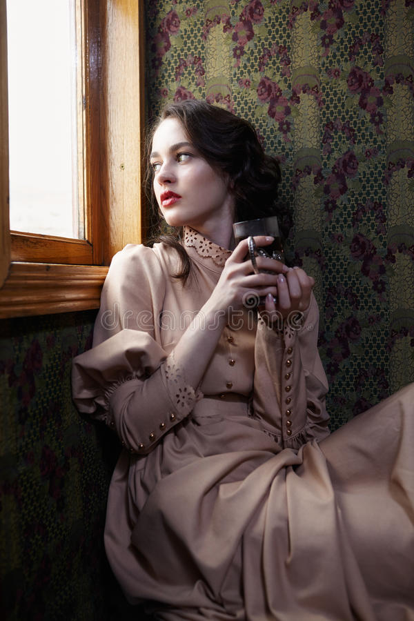 Young woman in beige vintage dress of early 20th century drinking tea in coupe of retro railway train stock photo