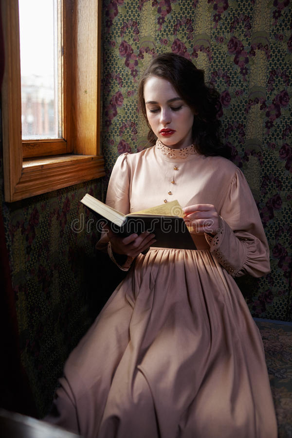 Young woman in beige vintage dress of early 20th century reading. Book in coupe of retro railway train stock photos
