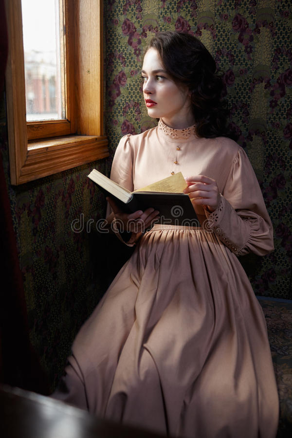 Young woman in beige vintage dress of early 20th century reading. Book in coupe of retro railway train stock images