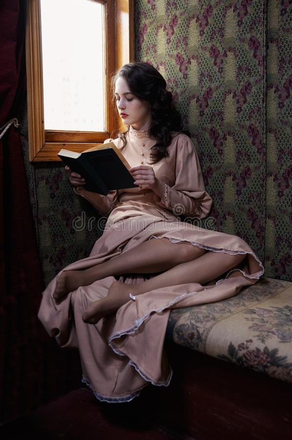 Young woman in beige vintage dress of early 20th century reading. Book in coupe of retro railway train stock image