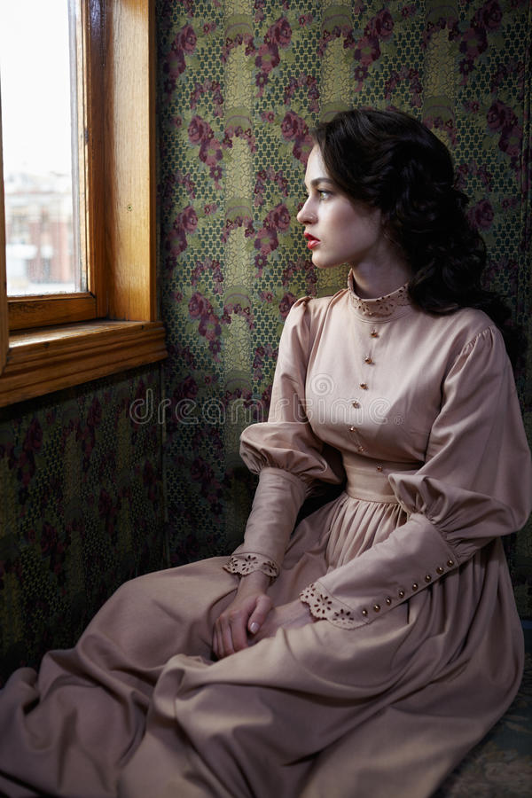 Young woman in beige vintage dress of early 20th century sitting. Young woman in beige vintage dress of early 20th century looking trough the window in coupe of royalty free stock photography