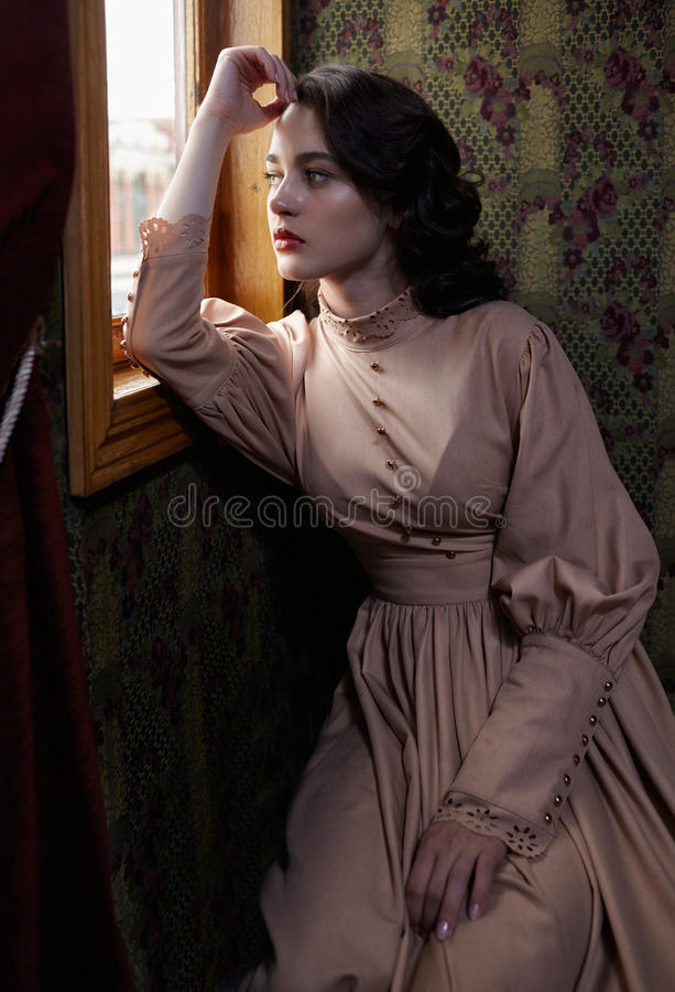 Young woman in beige vintage dress of early 20th century sitting. Young woman in beige vintage dress of early 20th century looking trough the window in coupe of royalty free stock image
