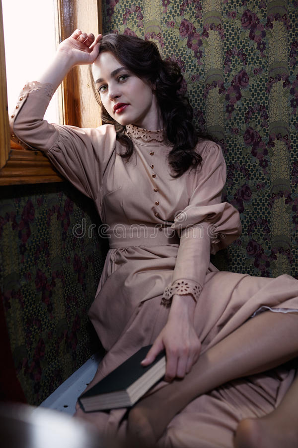 Young woman in beige vintage dress of early 20th century sitting. Near window in coupe of retro railway train stock photo