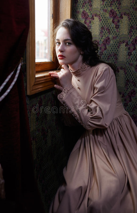 Young woman in beige vintage dress of early 20th century sitting. Near window in coupe of retro railway train stock image