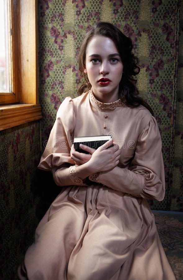 Young woman in beige vintage dress of early 20th century sitting. Near window in coupe of retro railway train stock photography