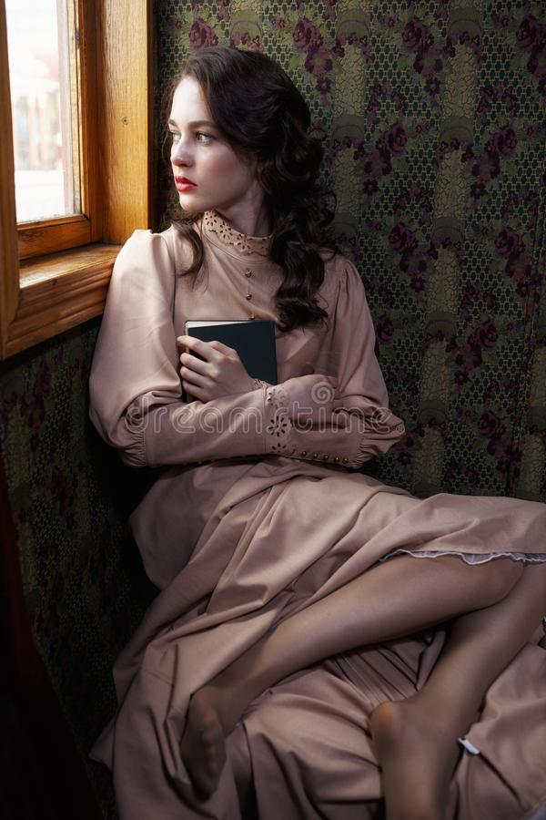 Young woman in beige vintage dress of early 20th century sitting. Near window in coupe of retro railway train royalty free stock photography