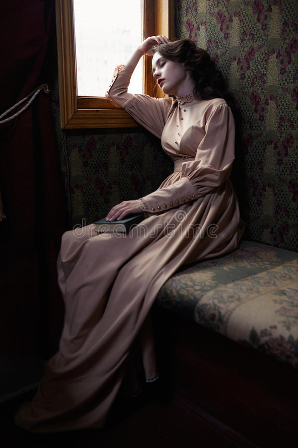 Young woman in beige vintage dress of early 20th century sleapin. G near window in coupe of retro railway train royalty free stock photography