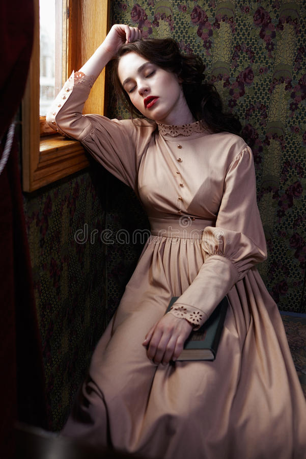Young woman in beige vintage dress of early 20th century sleaping near window in coupe of retro railway train royalty free stock photos